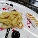 Tagliatelle di crepès con meringa dorata servita con salsa al cioccolato ed amarena