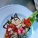 Fagottino di bresaola ripieno  con tagliatelle all'arancia e porcini su letto di rucoletta selvatica scaglie di grana e glacee di aceto balsamico ( scring de livign )