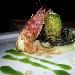 Rollè di branzino con gamberi rossi e pistacchi in foglia di lattughina su vellutata di patate al limone e capperetti di Pantelleria con bavarese di melanzane