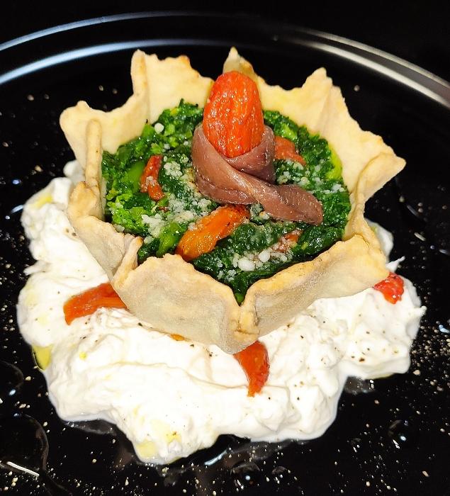 Cestino di pasta tarallo con broccoletti, acciughe e datterini confit su stracciatella di burrata