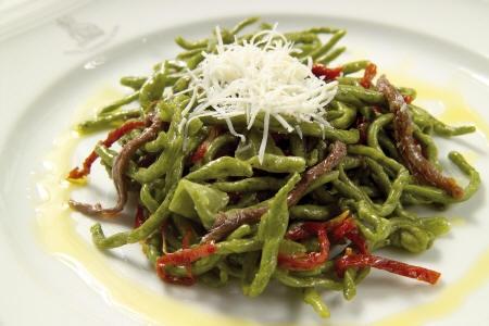 Strozzapreti verdi dello chef con pomodori secchi, filetti di acciughe, cacioricotta e olio extravergine di oliva