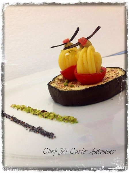 Coppia di anelli di spaghetto allo zafferano e pistacchi in coppe di ciliegino e melanzane