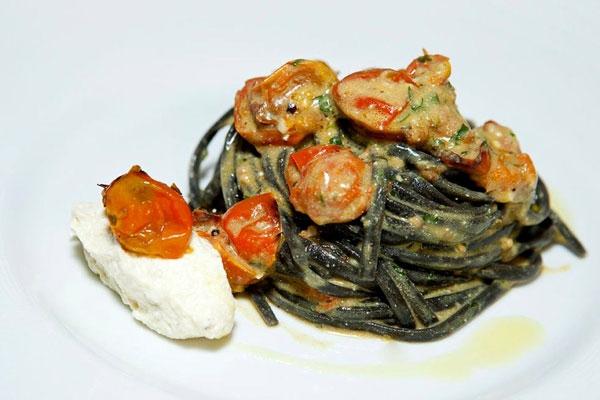 Linguine al nero di seppia con pesto di rucola, pomodorini cotti al forno ed emulsione di ricotta al limone