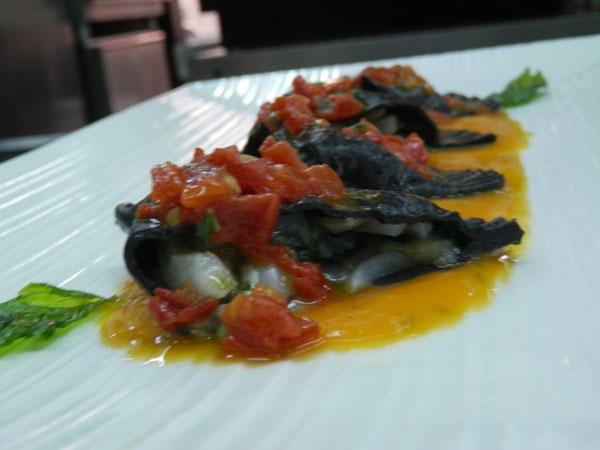 Raviolacci neri farciti con seppie e bieta costa in salsa di pomodoro datterino su crema vellutata di zucca e menta