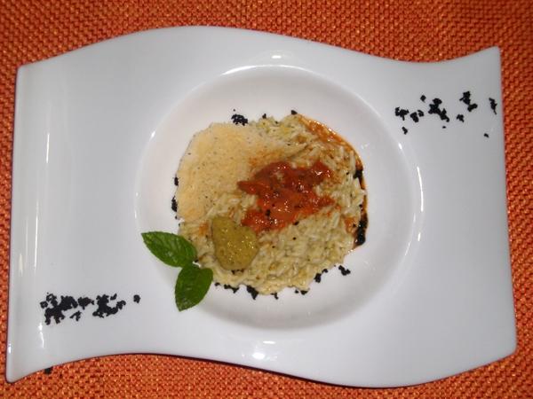 Risotto al pesto di pistacchio di Bronte con emulsione di uova di ricci e polvere di olive nere