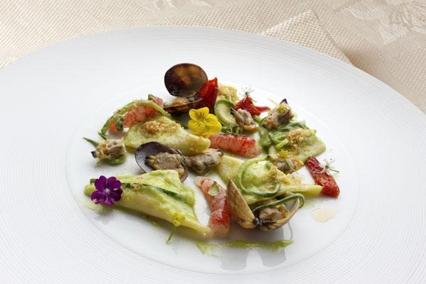 Raviolo di pasta cotta ripieno di ricotta e limone, salsa di zucchine, vongole, gambero rosso e briciole di pane