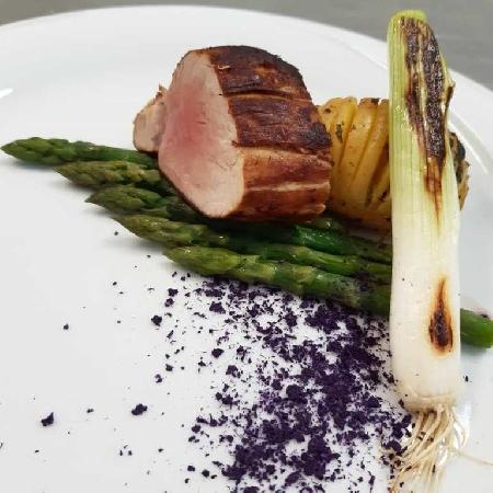 -Filetto di maiale affumicato con asparagi al burro, patate hasselback, cipollotto piastrato e polvere di cavolo viola