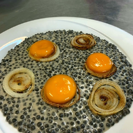-Fregola al nero di seppia mantecata alla cipolla PAT sarda servita con uovo marinato